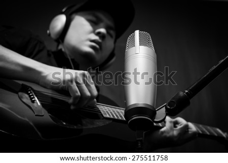 singer,guitarist,musician play guitar on condenser microphone in music recording studio / black and white processed - stock photo