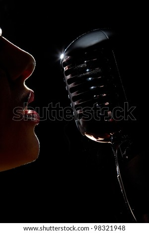 Singer in front of a microphone. Isolated on a black background