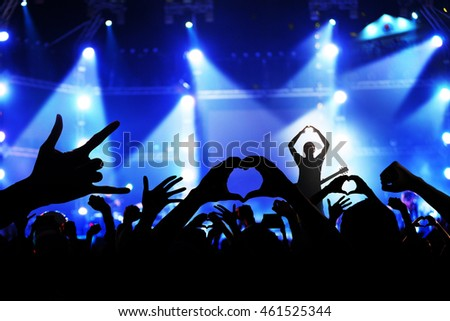 Singer on concert stage with ray of illuminated and crowd of cheering fans in music concert