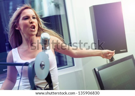 Singing a beautiful girl with a microphone - stock photo