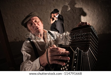 Singing bandoneon player with two dancers in the background