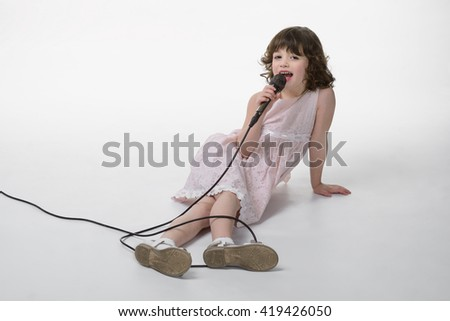 Singing beauty with cable from microphone braided around her legs. Caucasian female lies on the ground in studio with an opened mouth. Isolated. - stock photo
