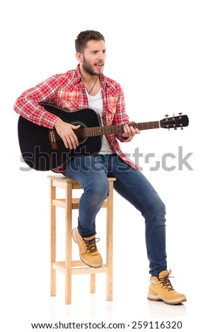 Singing guitarist in red lumberjack shirt sitting on a chair play the black acoustic guitar. Studio portrait isolated on white.