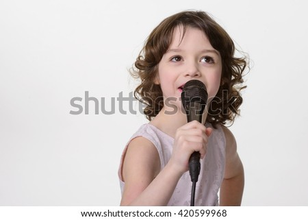 Singing lovely girl hold black microphone with cable in her hands. Small kid looks upwards. Close-up portrait of pretty young lady with curled brunette hair. - stock photo