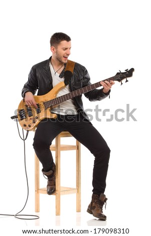 Singing male guitarist sitting on a chair and playing the bass guitar. Full length studio shot isolated on white. - stock photo