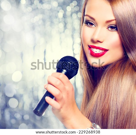 Singing Woman. Beautiful model Girl Singing. Beauty gorgeous lady with Microphone over holiday glowing Background. Singer. Karaoke song, party  - stock photo