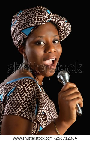 Singing young Ghanese african woman against a black background - stock photo