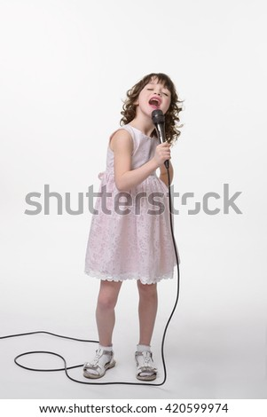 Singing young princess with an opened mouth and closed eyes from pleasure. Caucasian female holds black microphone in her hand.  - stock photo