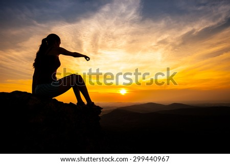 single adult woman silhouette on rock pointing on landscape