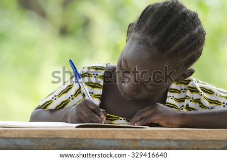 Single African Schoolgirl Writing Learning Doing her Homework - stock photo