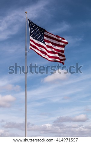 Single American Flag with a cloudy blue sky background.