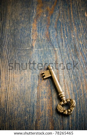 single antique key sitting on a wood table - stock photo