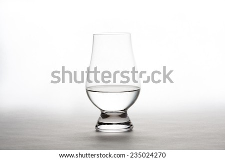 Single backlit crystal glass containing vodka, gin moonshine, or tequila.  White background with copy space in upper part of image. - stock photo