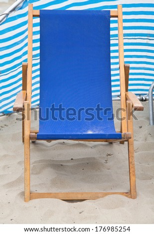 Single beach chair before wind screen front - stock photo