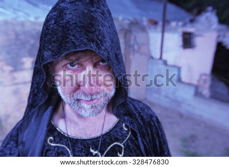 Single bearded male witch in black cloak - stock photo