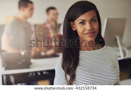 Single beautiful female business owner wearing black and white striped blouse with two employees on computer in background - stock photo