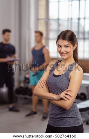 Single beautiful fit young woman in gray tank top with folded arms and confident expression at gym