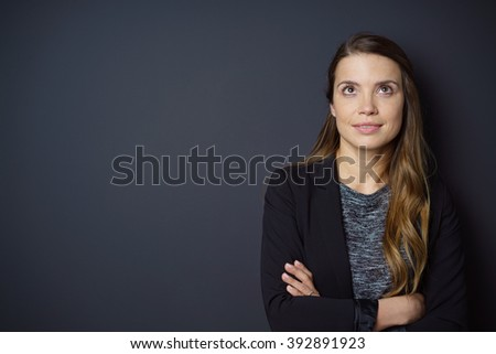 Single beautiful grinning woman in black jacket and long brown hair with folded arms looking up over dark background with copy space