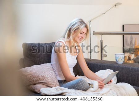 Single beautiful smiling woman in sleeveless shirt and pants with white dots relaxing on sofa while reading tablet computer next to coffee mug