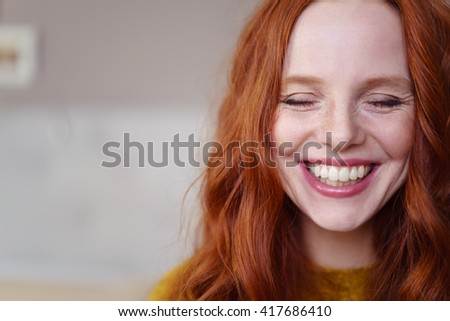 Single beautiful young Caucasian woman with long red hair and closed eyes next to copy space - stock photo