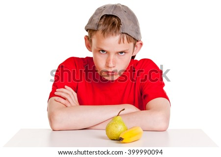 Single belligerent young boy in red shirt and backward hat with folded arms next to green pear and yellow banana over white background - stock photo