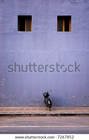 Single bicycle parked next to a lilac building facade.