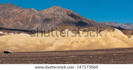Single black car trying to get over Death Valley desert, California, USA