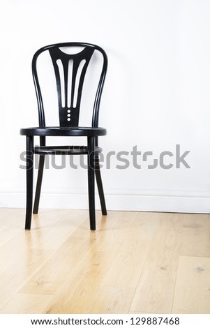 Single black modern chair on a pine floor against a white wall - stock photo