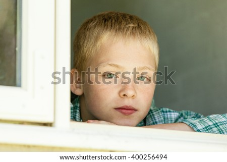 Single blond boy wearing flannel shirt, chin resting on arms and serious expression looking out from window - stock photo