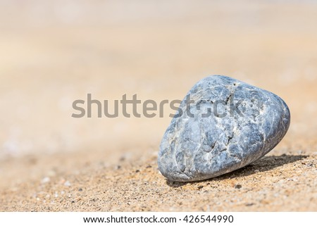 Single blue textured rock on sand, low angle view, shallow depth of field. Rock contour with hard shadow for artistic effect. Heavily blurred background. Copy space.  - stock photo
