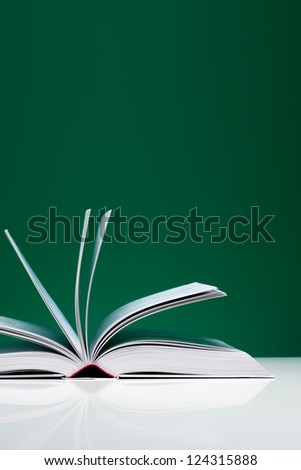 Single book on a white desk with flying pages over green background. - stock photo