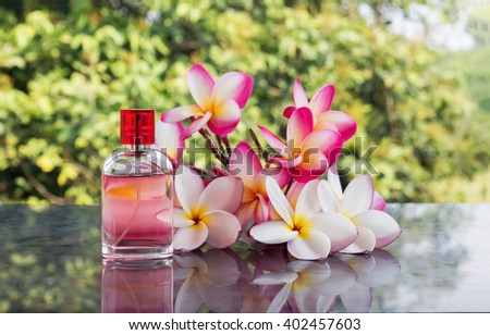 Single bottle of sweet pink fragrant perfume decorated with pink and white flower frangipani or plumeria and tree background