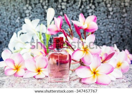 Single bottle of sweet pink fragrant perfume decorated with pink flower plumeria