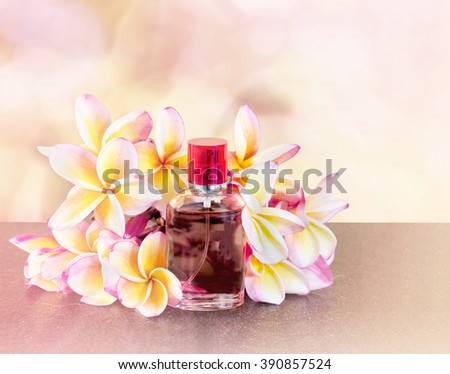 Single bottle of sweet pink fragrant perfume with pink flower plumeria or frangipani and sweet abstract background