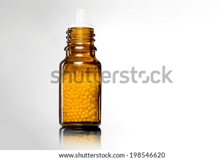 single bottles with homeopathy globules,white white background. - stock photo