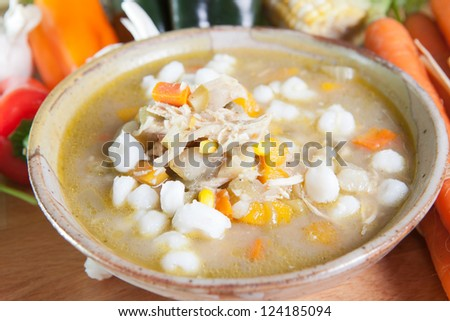 Single bowl or serving of southwestern style chicken posole garnished with carrots, peppers, garlic, and hominy. - stock photo