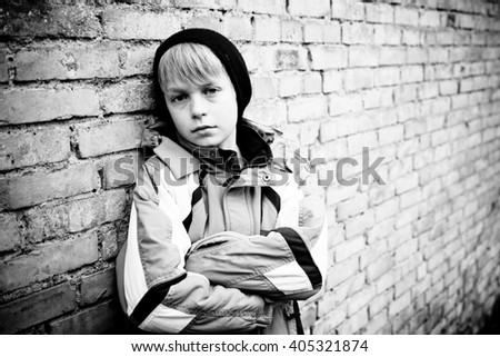 Single boy in winter coat and black hat with folded arms and sad facial expression next to old brick wall outdoors - stock photo