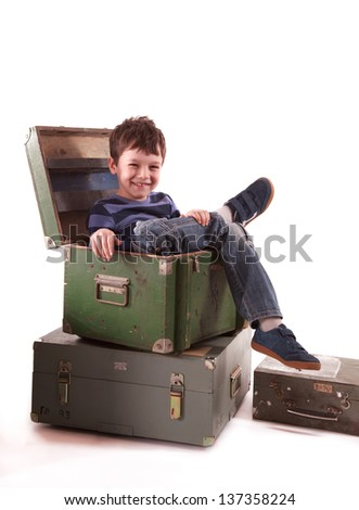 single boy sitting in wooden box looking to the camera
