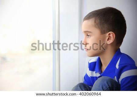 Single boy sitting on windowsill indoors - stock photo