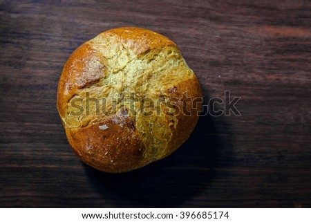 single bread on wood board - stock photo