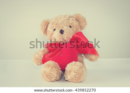 Single brown teddy bear tied red bow and red heart yarn front side. with copy space for write text vintage style.