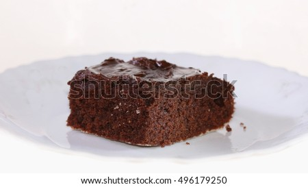 Single brownie piece with ground coconut and chocolate topping on plate