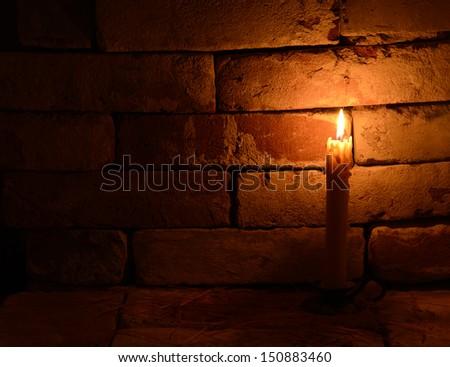 Single burning candle on the brick background in night 3 - stock photo