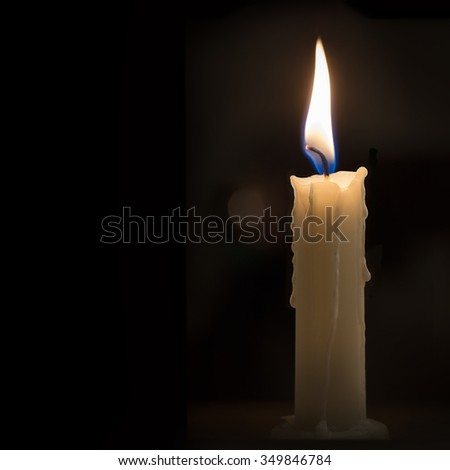 Single candle burning in dark room, with space for text.