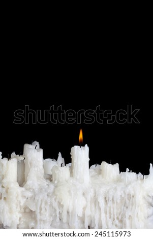 single candle burning on a black background with space for text