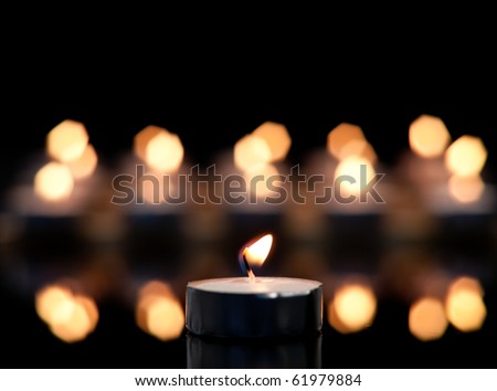 Single Candle Focused with Out of Focus Candle Bokehs in Background - stock photo