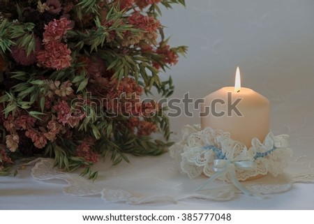 Single candle in a wedding garter with a bouquet of dried oats and flowers on festive embroidered white tablecloth - stock photo
