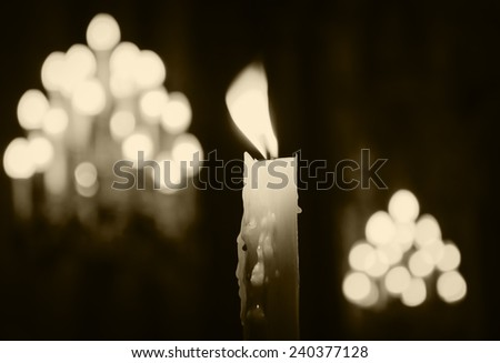 Single candle with dripping wax and blurring lights of many candles in two candlesticks at background. Aged photo. Sepia.