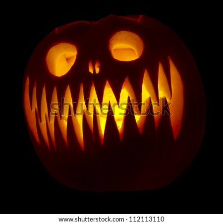 Single carved pumpkin with candle inside lit up in the dark - stock photo