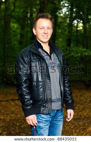 Single casual young man in forest. Short hair wearing jeans and black leather jacket.